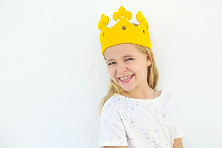 Portrait of smiling girl wearing crown against white wall
