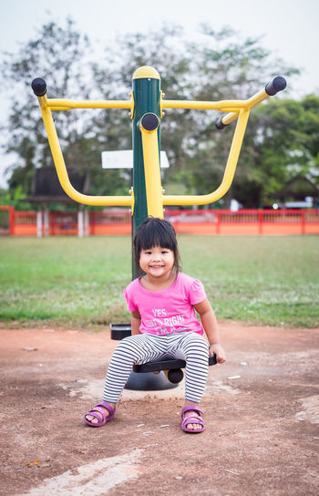 Full length portrait of cute girl sitting on exercise machine in park