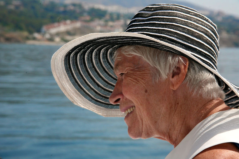 Smiling Aged Woman Wearing Hat Against Lake