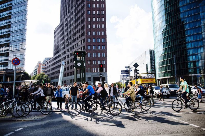People riding bicycles on street against buildings in city