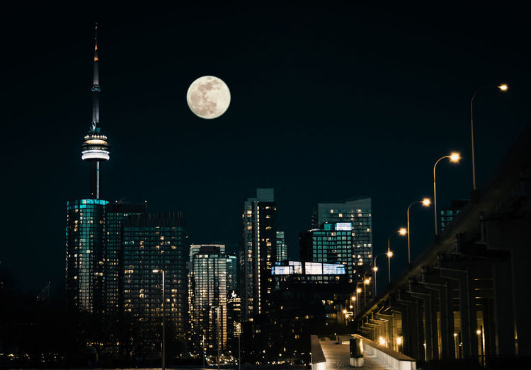 Low angle view of moon over illuminated buildings at night