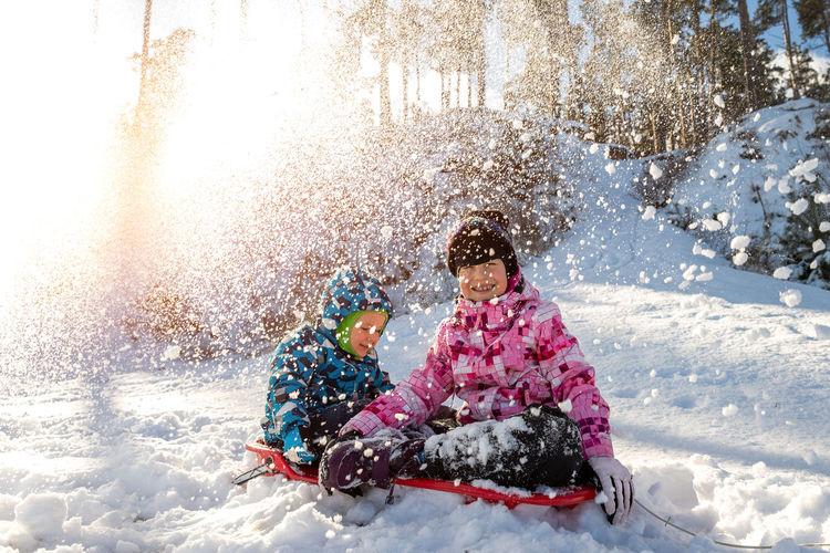 Full length of girl sitting on snow