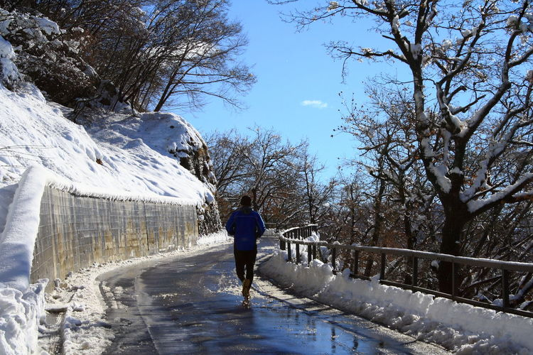 Rear View Of Person Jogging On Wet Road During Winter