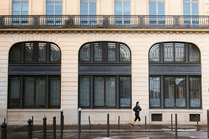 A masked woman runs through Place de la Bourse, Paris. Architecture Running Runner Woman Mask Morning Plaza Bourse Paris Building Exterior Built Structure One Person Outdoors City EyeEmNewHere first eyeem photo