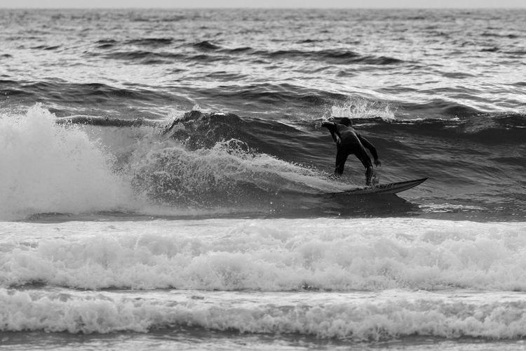 Man surfboarding on waves in sea
