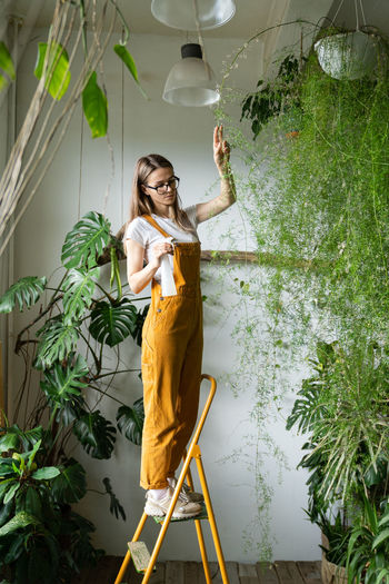 Young woman by potted plants