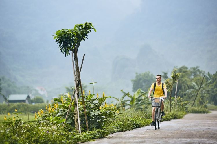 Man riding bicycle by land on road