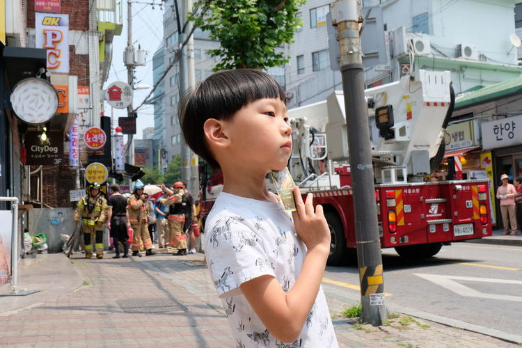 Portrait Child Boy EyeEm Selects People Fire Truck Fire Fighters Street Outdoors Looking Mobility In Mega Cities Real People Day City Life City #urbanana: The Urban Playground This Is Natural Beauty