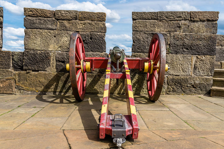 An antique cannon in red-yellow color on the walls of a medieval castle.