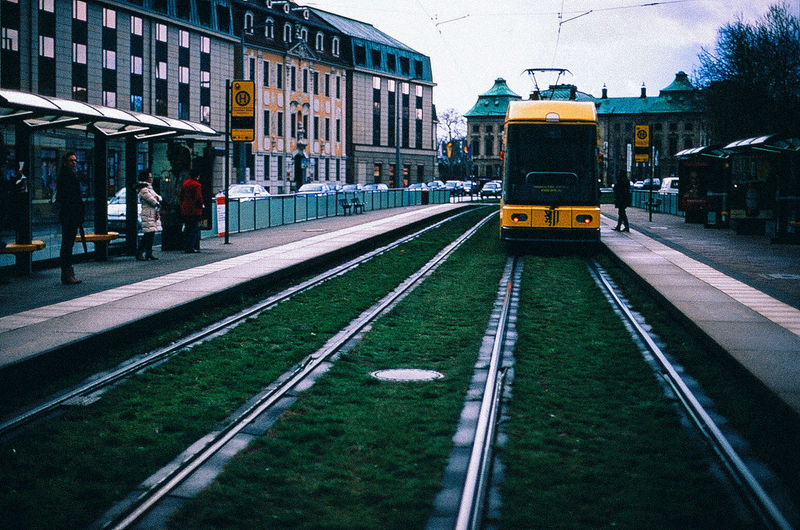 Yellow Train On Railroad Track By Buildings In City