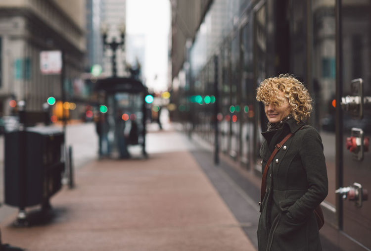 Woman Standing On Sidewalk In City