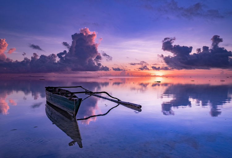 Boat moored in sea against sky during sunset