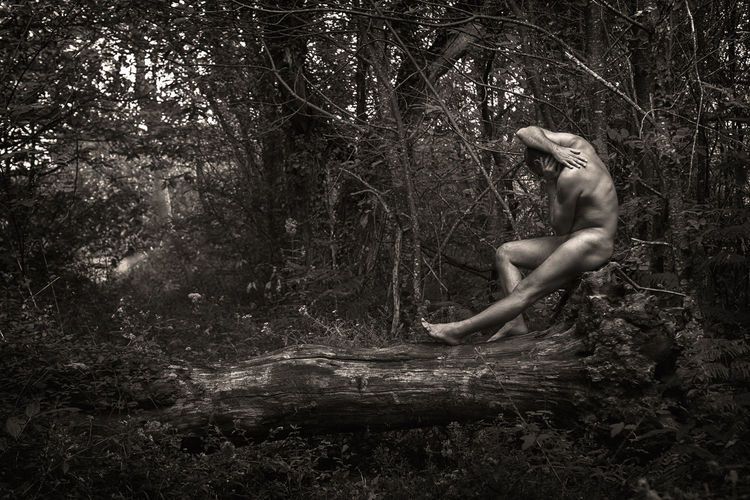Side view of naked man sitting on fallen tree in forest