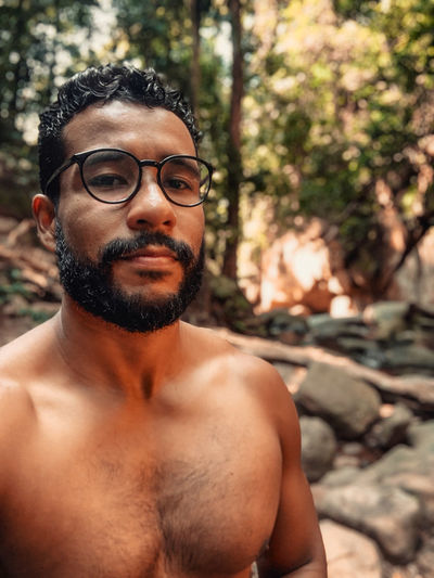 Portrait of shirtless man standing in forest