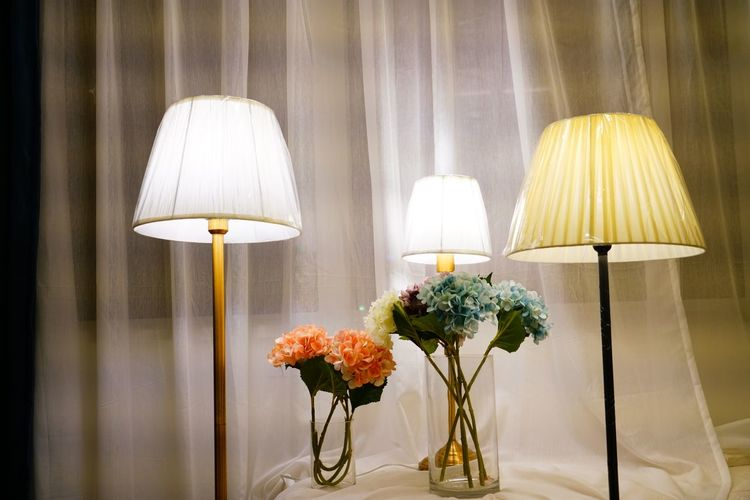 Illuminated lamps with flower vases at home