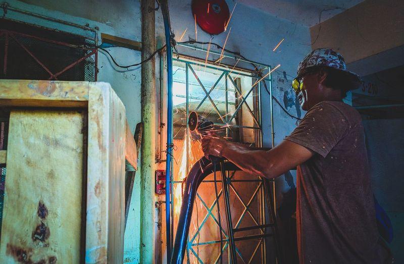 Side view of man welding metal in workshop