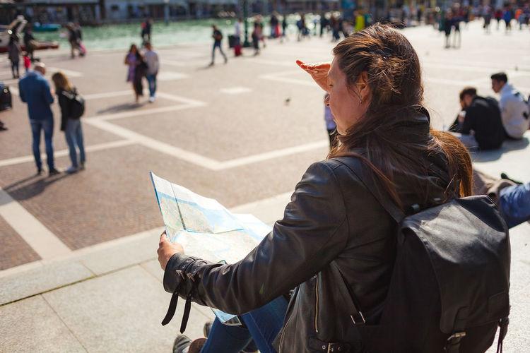 Dark haired girl looking at venetian paper map sitting on santa luchia square