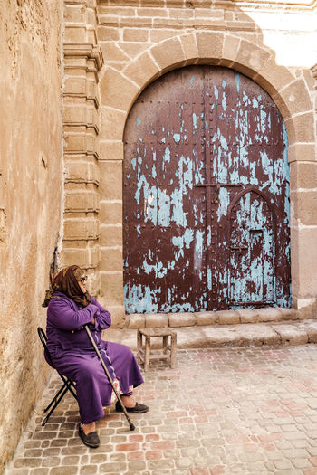 Woman standing against building wall