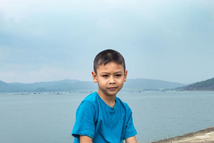 Portrait of boy sitting against sea
