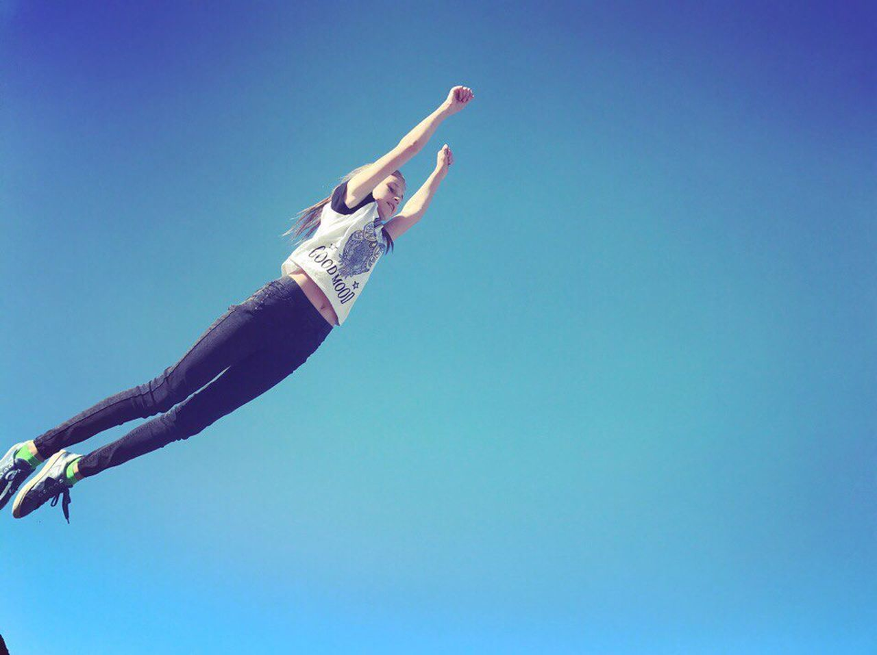 sky, one person, blue, copy space, low angle view, clear sky, human arm, human body part, nature, limb, day, adult, mid-air, full length, jumping, human limb, outdoors, arms raised, flying