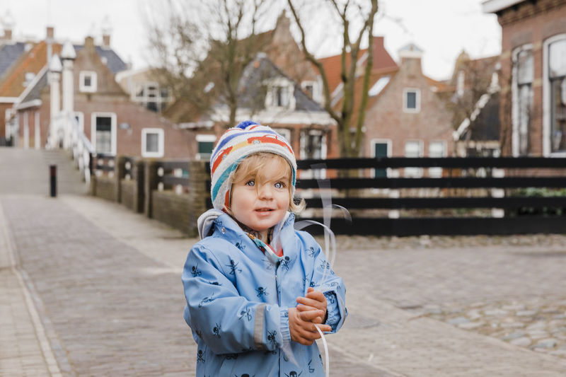 Toddler girl in old village – Hindeloopen, Friesland, Netherlands Architecture Exploring Netherlands Ribbon Standing Winter Building Exterior Built Structure Child Childhood Cute Girl House One Person Outdoors Pavement Playing Portrait Street Toddler  Town Village Waist Up Warm Clothing Watching