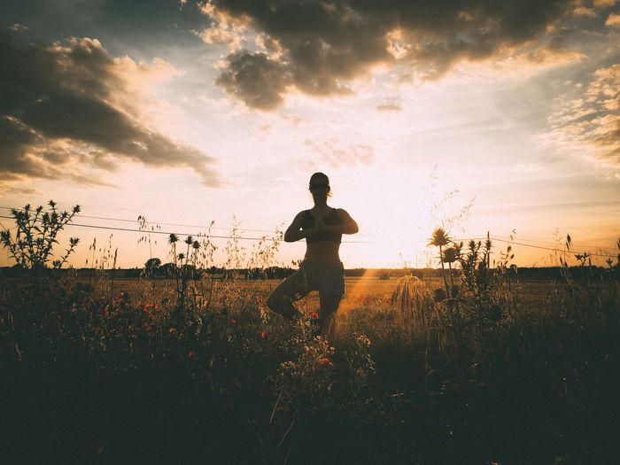 Woman meditating on field against cloudy sky during sunset