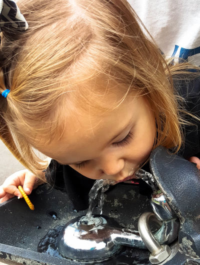 Close-Up Of Thirsty Girl Drinking Water From Faucet