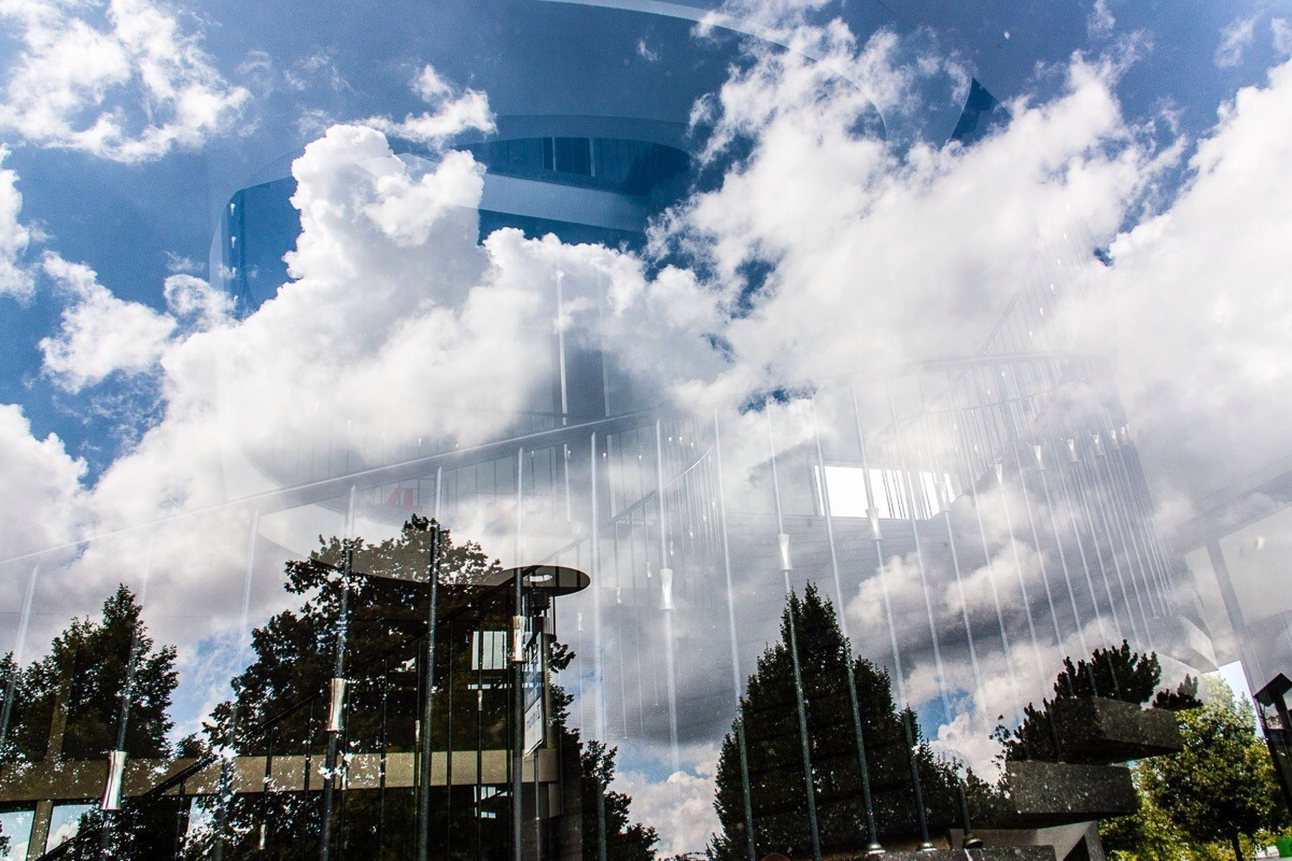 built structure, architecture, sky, building exterior, cloud - sky, tree, cloudy, low angle view, glass - material, city, modern, cloud, day, building, reflection, weather, travel destinations, outdoors, no people, travel