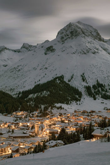 Lech by mountain against sky during winter