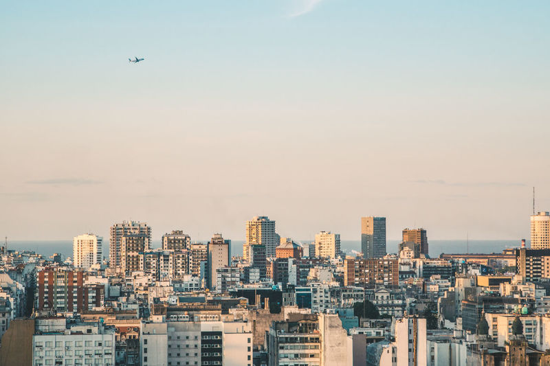 A plane taking off over the skyline of Buenos Aires. Fly Gradient Plane Soft Take Off Travel Airplane Architecture Building Exterior Built Structure City Cityscape Downtown Flying Horizon Over Water Minimal Minimalism Modern No People Ocean Outdoors Sky Skyline Skyscraper Tall An Eye For Travel The Graphic City Adventures In The City Visual Creativity This Is Latin America The Great Outdoors - 2018 EyeEm Awards The Traveler - 2018 EyeEm Awards A New Beginning Capture Tomorrow A New Perspective On Life Humanity Meets Technology