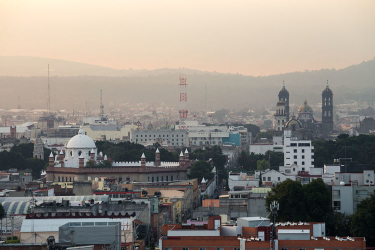 Sunrise in the city of Puebla de Zaragoza, Mexico Catedral Cathedral Roof Architecture Belief Bell Tower Building Building Exterior Built Structure City Cityscape Crowd Crowded Fog High Angle View Mountain Range Nature Outdoors Place Of Worship Religion Residential District Sky Spirituality Sunrise Sunset