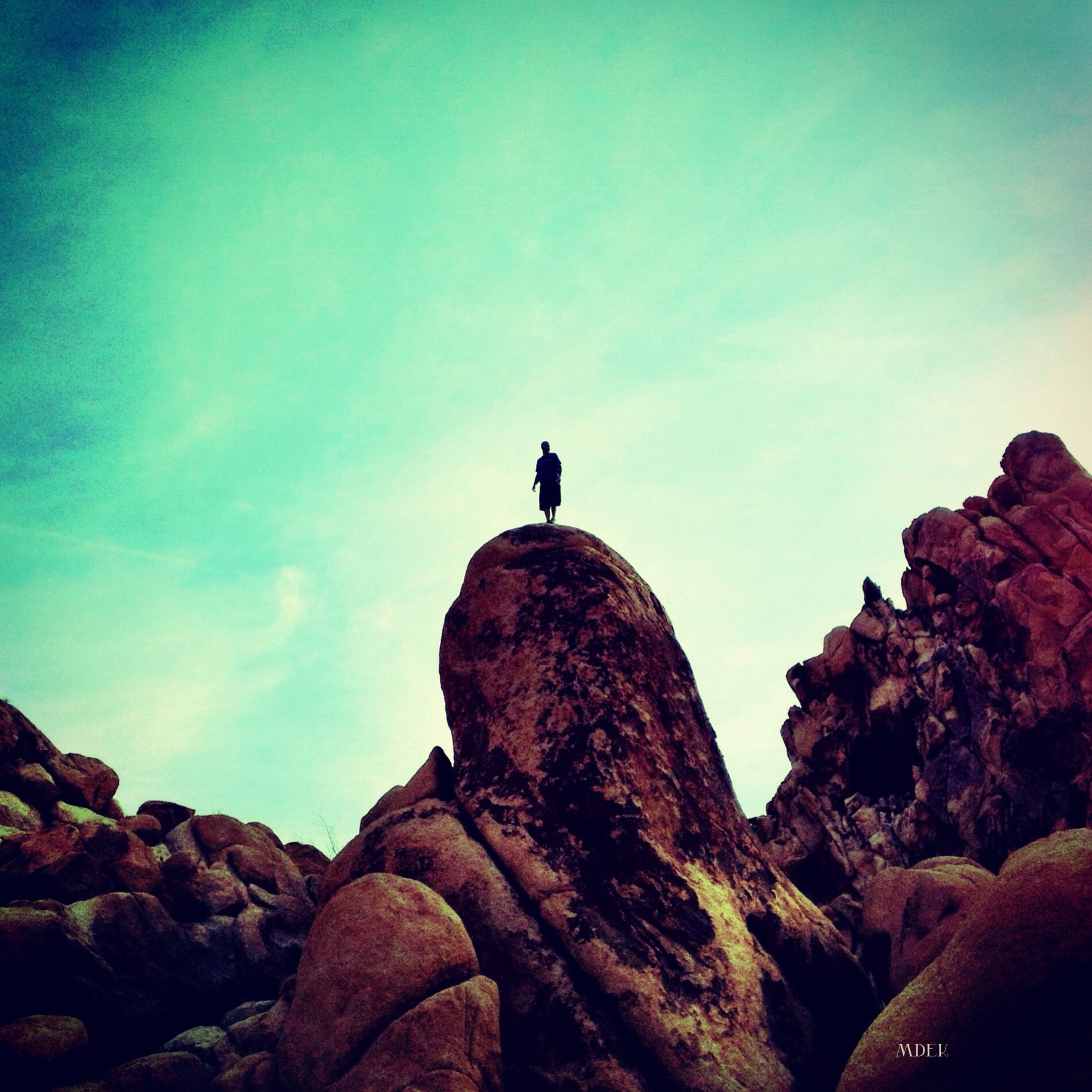 rock - object, sky, low angle view, bird, silhouette, one animal, tranquility, nature, rock, rock formation, beauty in nature, full length, tranquil scene, scenics, animal themes, copy space, blue, wildlife, animals in the wild, clear sky