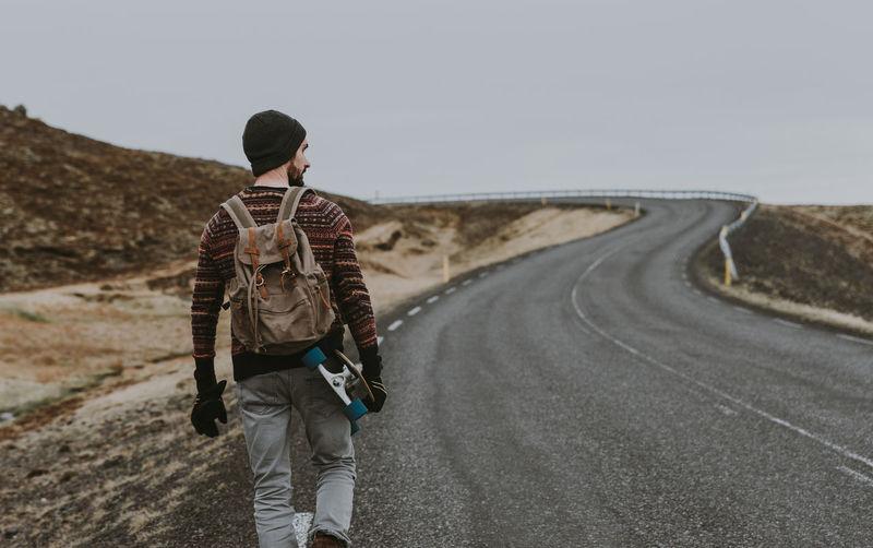 Man walking with skateboard on highway