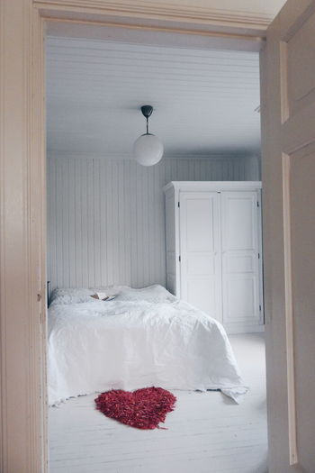 Rose Petals In Heart Shape At Bedroom Seen Through Doorway