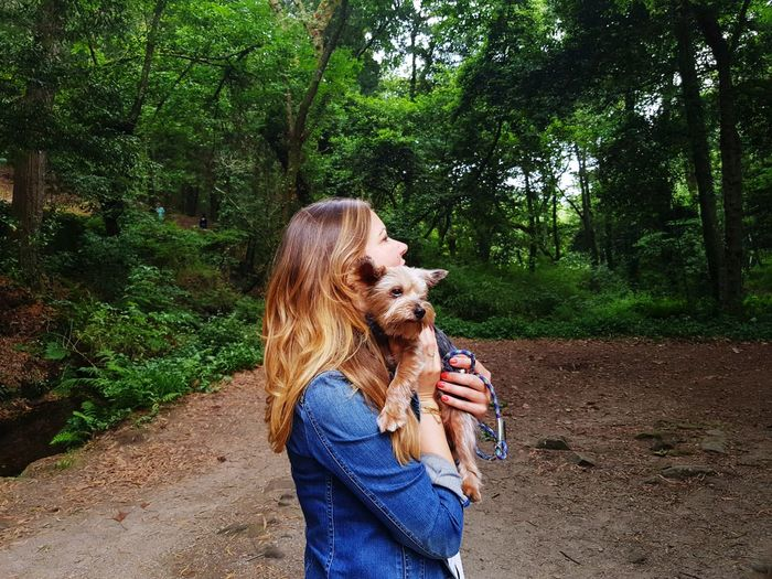 Side View Of Woman Holding Dog At Forest