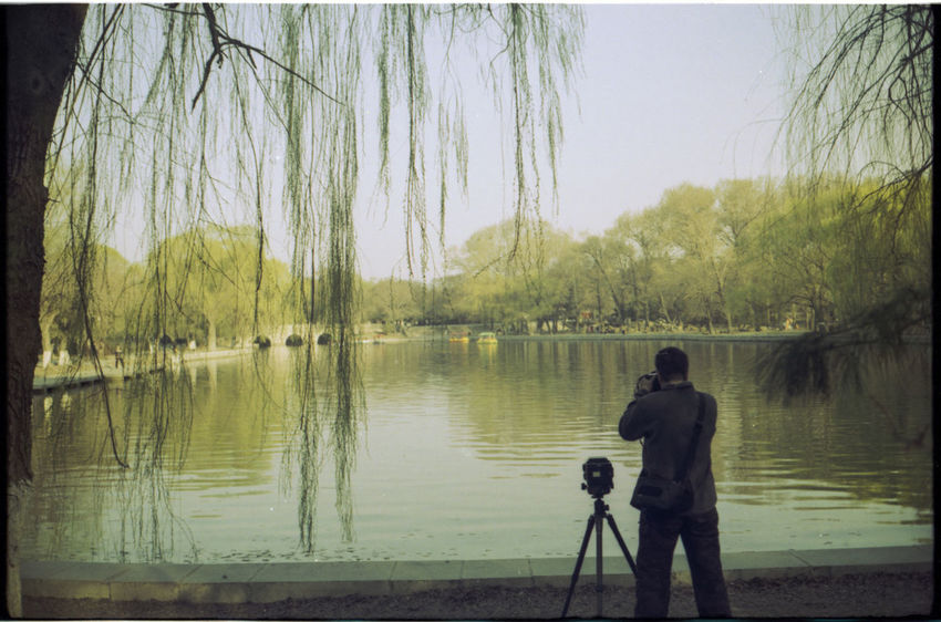 Analogue Photography Day Lake Leisure Activity Nature One Man Only One Person Outdoors Photographer Real People Rear View Sky Standing Sunset Tree Trees Water