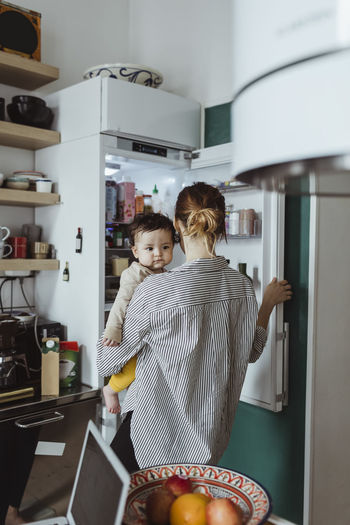 Rear view of people standing in kitchen at home