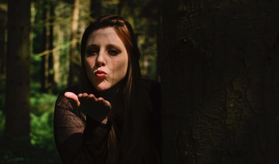 Portrait of young woman blowing kiss while standing behind tree trunk in forest