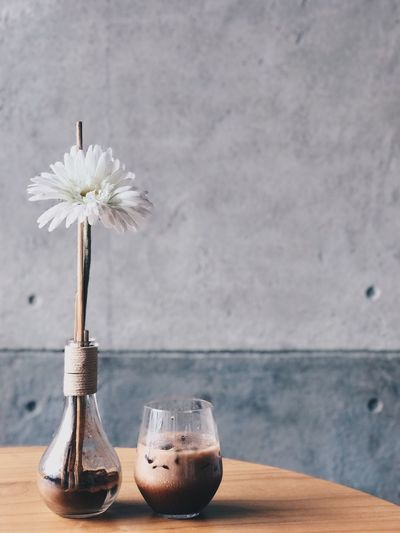 Close-Up Of White Flower In Vase With Coffee On Wooden Table Against Wall