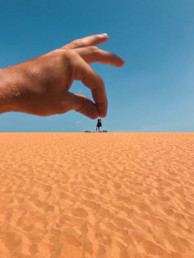 Travel Destinations Creativity Having Fun Horizon Clear Sky Tiny People Humor Vietnam Vertical Sand Dunes Illusion Human Hand Hand Land Sand Sky One Person Real People Clear Sky Nature Human Body Part Desert Blue Landscape Beauty In Nature Environment Travel Leisure Activity Men Outdoors