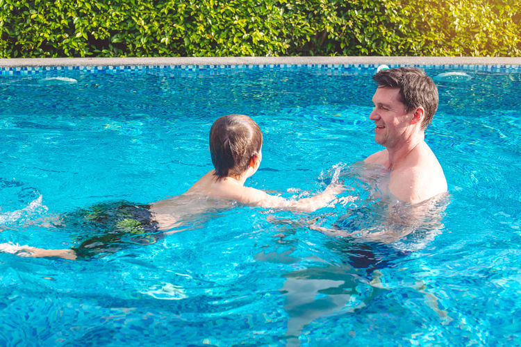 Father and son swimming in pool