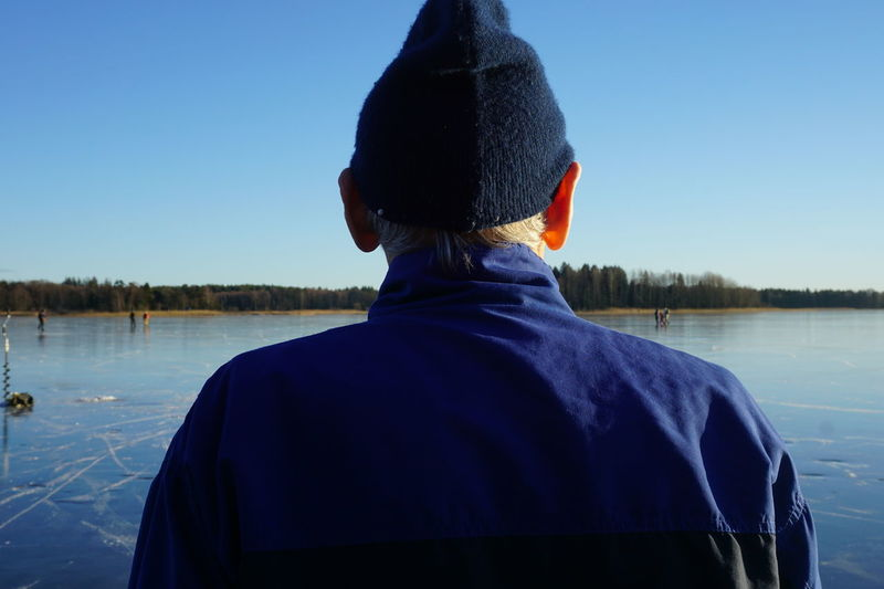 Rear view of senior man standing by lake against clear blue sky