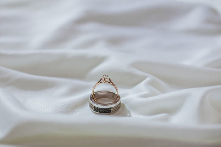 High angle view of wedding rings on bed