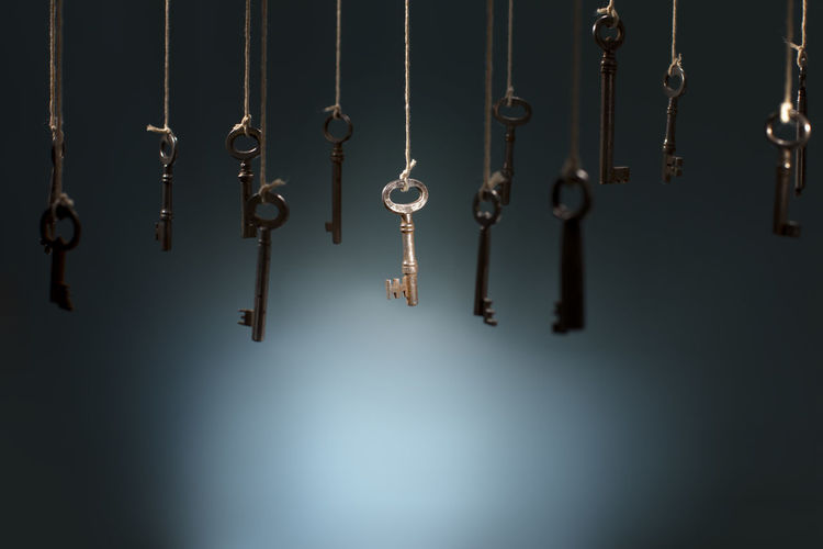 Old keys hanging on strings. One key in the middle is in spotlight focus. Hanging Indoors  Metal No People Key Close-up In A Row Side By Side Group Of Objects Large Group Of Objects Studio Shot uniqueness Chosen Paths Outdoors