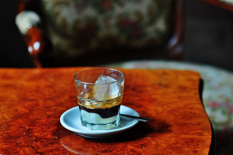 Close-up of espresso with ice in glass on table