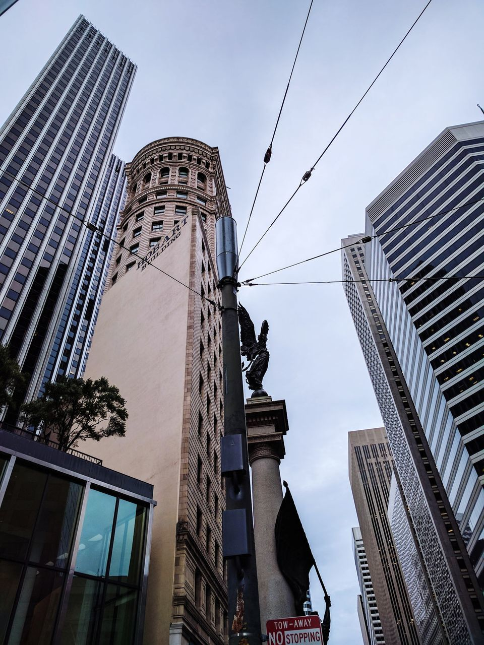 architecture, building exterior, built structure, skyscraper, low angle view, sculpture, city, statue, modern, outdoors, day, sky, travel destinations, no people