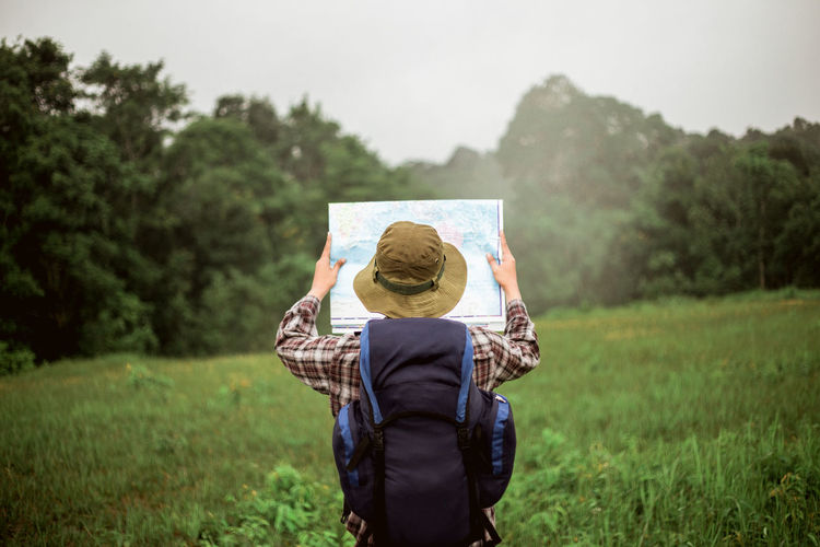 Rear view of man reading map while standing on land