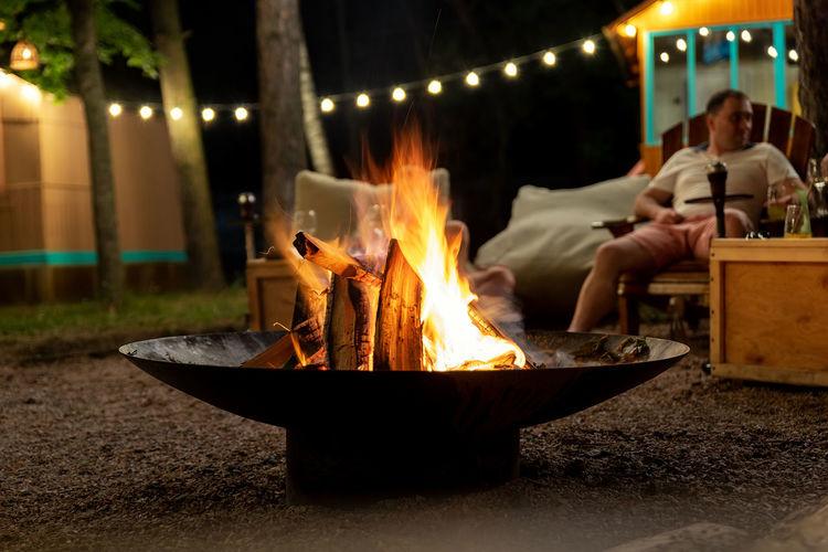 People sitting on bonfire at night
