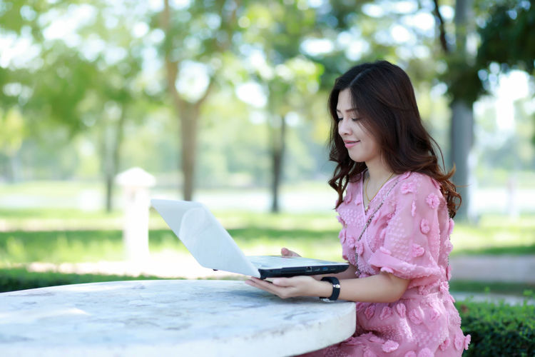 Side view of young woman using mobile phone outdoors