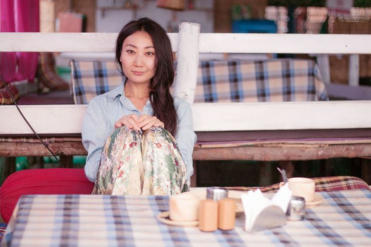Portrait of smiling young woman sitting at cafe